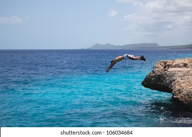 A young man dives off a small cliff in to the ocean  in Bonaire