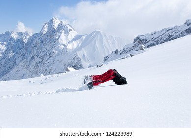 Young man diving head first into untouched powder snow with panorama of mountains in background