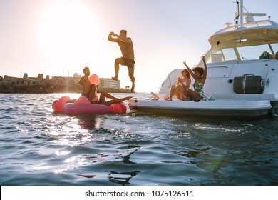 Young man diving into the sea from yacht with friends cheering. Group of friends having a great summer vacation.