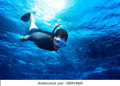 young man diving snorkeling down into the deep blue ocean sea against the sunlight
