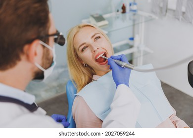 Young man doctor in dentist binocular loupe mask drills tooth of patient european woman with caries decay sit at dentist office chair indoor cabinet near stomatologist. Healthcare enamel treatment.