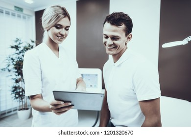 Young Man with Doctor in White Coat in Clinic. Medical Equipment. Healthcare Concept.Smiling Toung Man. Smiling Woman in Uniform. Modern Clinic. Patient in Hospital.