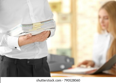 Young man with documents in office
