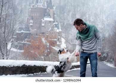 young man and a dog at the castle. Walk with your pet. australian shepherd on nature in winter.