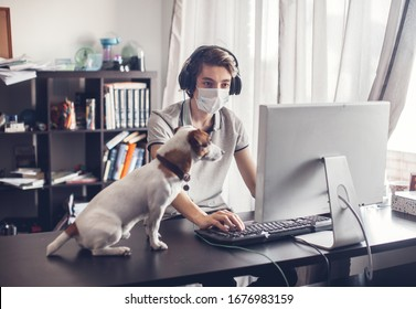 Young man with dog in quarantine. Online distance learning. Teen gaming at home with computer, wearing protective mask.