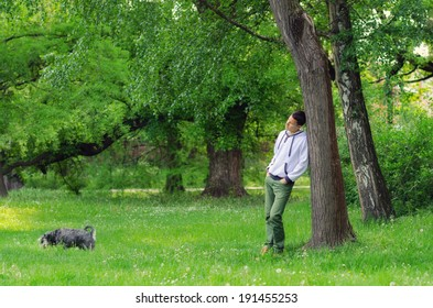 Young man with dog walking in the forest on sunny spring day.