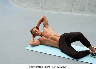 Young Man Doing Abs Workout On Yoga Mat Against Concrete Wall Outdoors. Topless Handsome Caucasian Sportsman With Strong Muscular Body In Fashion Sportswear On Functional Training.