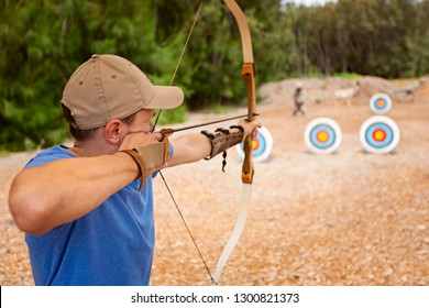 young man doing archery, aiming at the target, fun outdoor activity concept