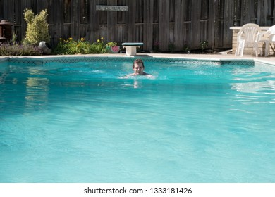 Young man doing breast stroke in an outdoor swimming pool on a sunny day. Fit white man swimming laps in an outdoor swimming pool in the summer. Diving board in the background. Exercising in pool.