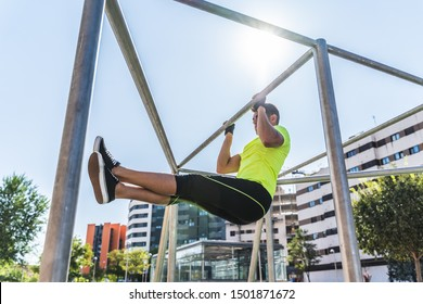 Young Man Doing Calisthenics Outdoors. Man Doing Pull-Ups in the Street. Guy Working Out on Pull-Up Bars. Latin American Man Exercising Outdoors. Sport Concept.