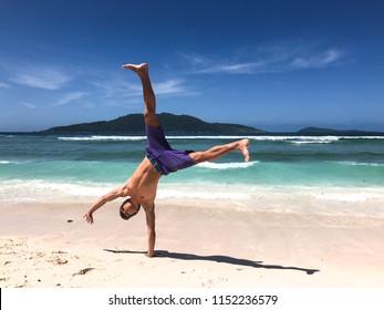 A young man doing a cartwheel at Anse Banane beach, La Digue, Seychelles