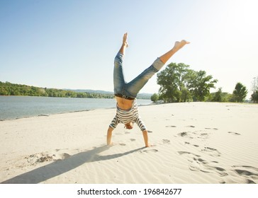 Young man doing a cartwheel on the beach