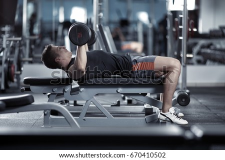Young Man Doing Chest Workout With Dumbbells