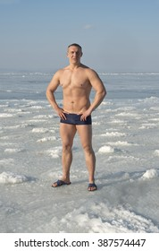 Young  man  doing  exercises  before  bathing  in  the  sea  ice  hole
