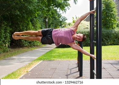 Young man doing exercises on vertical bar outdoors in park, performing human flag figure.