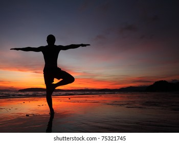 Young man doing exercises on wet sand