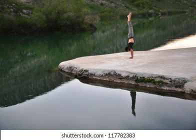 Young man is doing handstand on the lake island. / Handstand / Shot was taken in Bosnia and Herzegovina