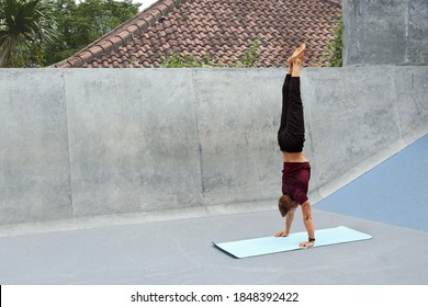 Young Man Doing Handstand On Yoga Mat Against Concrete Wall Outdoors. Handsome Caucasian Sportsman With Strong Muscular Body In Fashion Sportswear Warming Up Before Intense Workout.