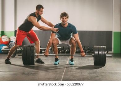 Young man doing hard workout with a personal trainer.
