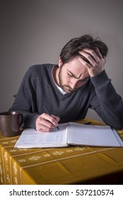 Young man doing homework, solving equations and calculating through problematic mathematics