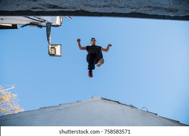Young man doing impressive parkour jump from one roof to another.