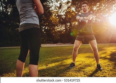 Young man doing kettlebell weight workout with personal female trainer in the park. Fit man swinging kettle bell with fitness instructor.