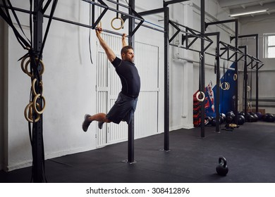 Young man doing kipping pull-ups exercise at gym