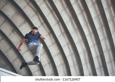 young man doing parkour jump in urban space in the city sunny spring summer day