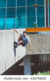young man doing parkour in urban space in the city  suuny spring summer day
