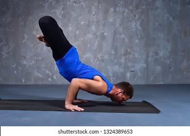 Young man doing the pose of yoga Urdhva padma vrikshasana