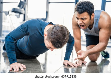 young man doing push-up and trainer yelling on him at sports center