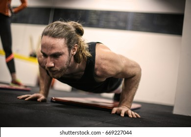 Young man doing push-ups in the gym. Man workout i  gym.