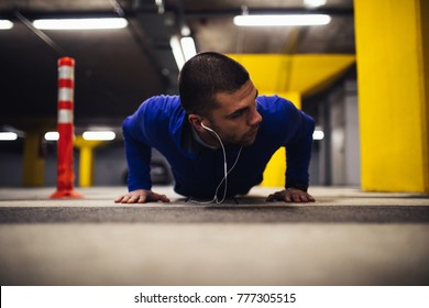 Young man doing pushups indoors