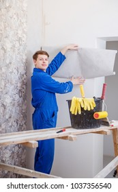 young man doing repairs in apartment, wallpapering on wall