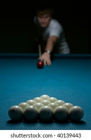 Young man doing shoot on billiard