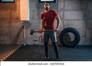 Young man doing sledgehammer exercises at the gym