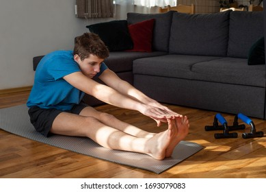 Young man doing stretching exercises at home. Stay home during COVID-19 quarantine  concept.