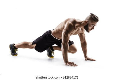 Young man doing stretching and warming up exercises. Photo of muscular man on white background. Sports