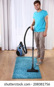 Young man doing vacuum cleaning in room