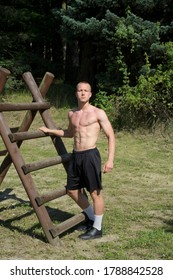 Young man doing workout using outdoor equipment.