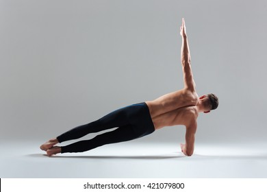 Young man doing yoga exercise isolated on a white background