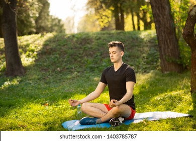 A young man doing yoga in the green park. Concept of a healthy lifestyle