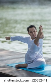 Young man Doing Yoga Pose in beautiful lakes background