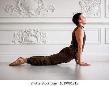Young man doing yoga in studio. Healthy lifestyle. Fitness workout. Lotus position and other asanas for reaching harmony inside body and beauty outside. Handsome and sexy. Warrior pose is his beloved.