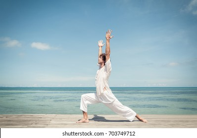 Young man doing yoga warrior pose on a beautiful tropical beach