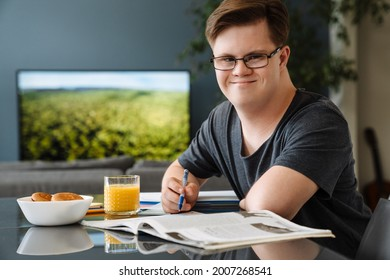 Young man with down syndrome smiling and doing home work in kitchen at home