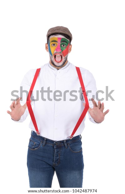 A young man drawing a clown on his face, wearing a suspenders and pulling it away with an open mouth, isolated on a white background.