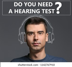 Young man with drawing of headphones and question DO YOU NEED A HEARING TEST on color background