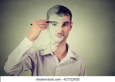 Young man drawing self portrait face, hiding true emotion isolated on grey wall background. Private life, identity concept.
