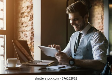 Young man drawing template for the web site associated with digital marketing, current trends and tendencies of UX / UI design. Businessman who rules his company remotely, like a freelancer